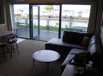 View from Living Room to Waterfront Patio with Dining Table and Chairs
