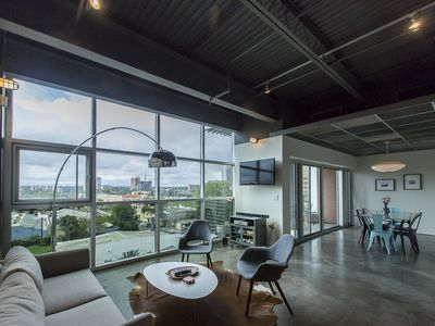 Stylish Loft with concrete floors, modern furnishings, floor-to-ceiling windows