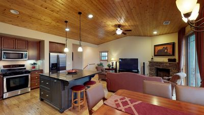 Picture taken from the dining area, displaying dining table, kitchen island, and oven and microwave. Living area visible in background.