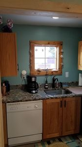 Dishwasher, coffee pot and cabinets with dishes, glasses, etc