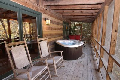 Screen-in porch with seating and hot tub