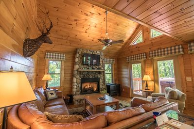 Living room with leather seating, gas log fireplace and large TV