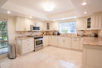 Spacious upgraded kitchen with granite countertops and stainless steel