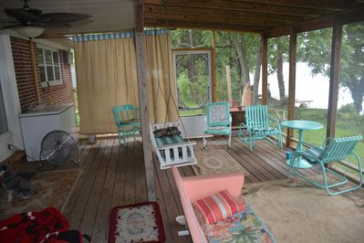 Lakeside screened porch is  favorite  gathering 424 spot with swing bed.