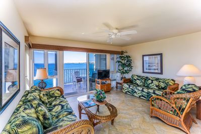 2 rattan couches and armchair facing TV and oceanfront lanai