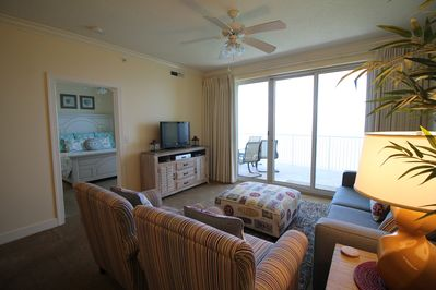 Living area with balcony access and flat panel tv