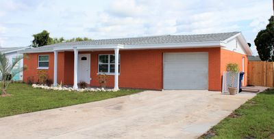Front of house with driveway and garay view