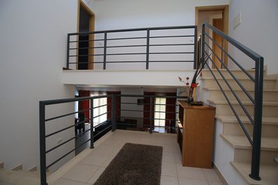 View of staircase on  villa with lower view onto open plan lounge/dinner