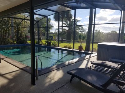 Large screen room covers pool, faces large back yard, boat dock, canal