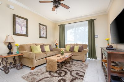 """Living room area with ceiling fan and 50"""" LCD screen. Screened pation beyond."""