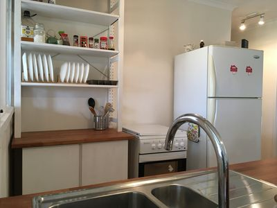 The kitchen has a full size fridge, electric stove and oven, a dishwasher
