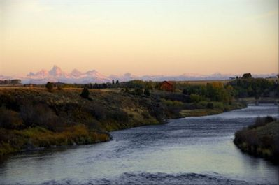 First snow on the Tetons as summer ends at Stonefly Lodge on the river.