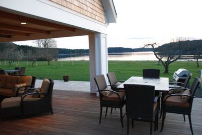 View of the covered porch out across the travertine patio, lawn and Westcott Bay