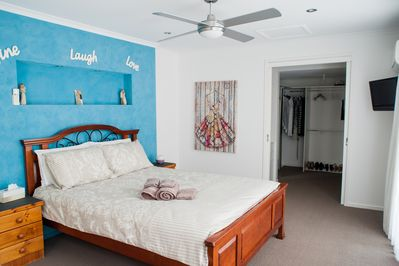 Master bedroom with walk in robe, safe, TV and air conditioning.