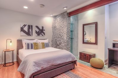 The 1st bedroom is an architectural delight with exposed stone and steel beams