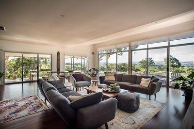 Open plan living / dining area with floor to ceiling windows over looking vines.