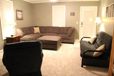 Spacious living room with sectional sofa, comfy rocking chair and futon sofa/bed