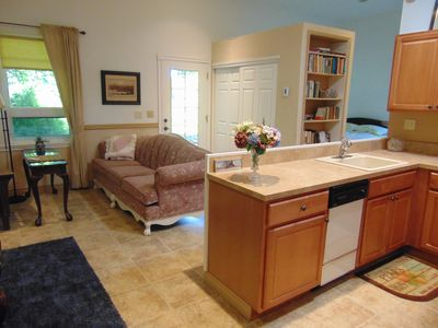 Kitchen sink, dishwasher, part of living area, closet, and glimpse of queen bed.