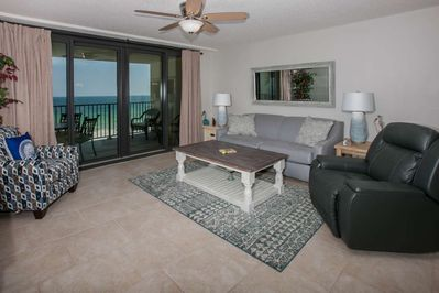 "Living room w/sleep sofa, side chairs, coffee and end tables, ceiling fan, 55"" flat screen TV and access to the Gulf-front balcony"
