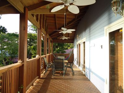 Deck running the length of the house with hammock, table and chairs