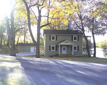 Roadside view of house with Tippecanoe River in background.