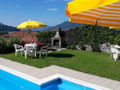 Photo for Apartment Il Bosso 102 with covered terrace just 100 meters from the lake and with large pool