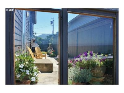 The side patio with glass gate leading to the beach.  Flowers, sunshine, BBQ.