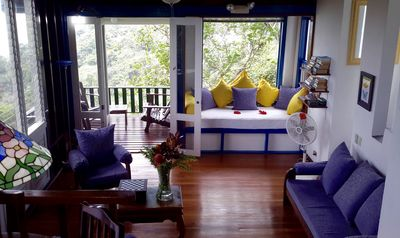 Living room, daybed (with yellow pillows) and one of two downstairs decks