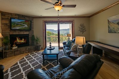 Living Room with stone fireplace, shuffle board table and amazing view