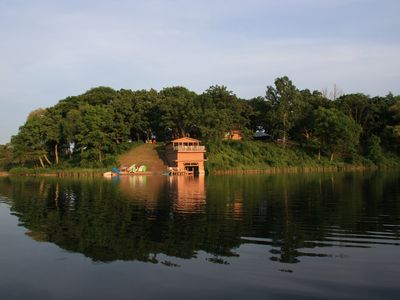 View of boathouse and beach from middle of private lake. Main house is in back.