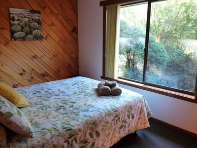 The queen bed in Boronia Cottage looks out into the bushland garden