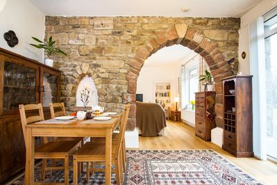 Looking through natural stone arch from dining area to sitting room