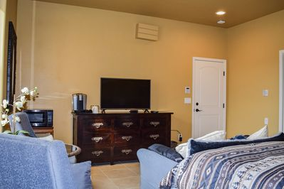 Wall opposite the bed, furnished with dark wood dresser, TV, Keurig, etc.