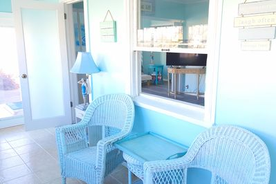 The front of the house features a glassed-in sunroom, perfect for morning coffee