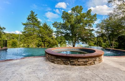 The in-ground hot tub and the infinity edge pool over looking the lake