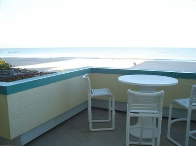 Front of balcony with beach and gulf view from high top seating.