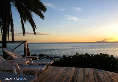Relax on Shell Villa's oceanfront deck as the sun goes down over gently smoking Montserrat
