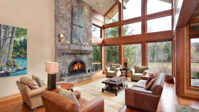 Living room with massive fireplace and exterior views overlooking Nicklaus North golf course