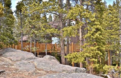 Tucked in the trees and rock formations with expansive log-railed deck