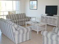 Upstairs lounge area with comfortable seating for 8 guests and large screen TV