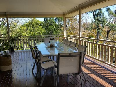 Large deck great for outdoor dining up with the trees and distant sea view.