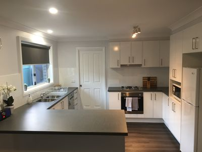 Fully equipped modern kitchen with gas stove, dishwasher, fridge & cookware
