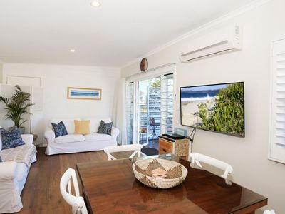 Lovely living area with double sofa bed and doors opening onto deck.