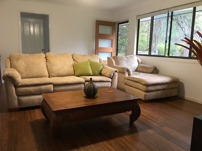 Comfortable suede lounge in open plan lounge room with flat screen tv