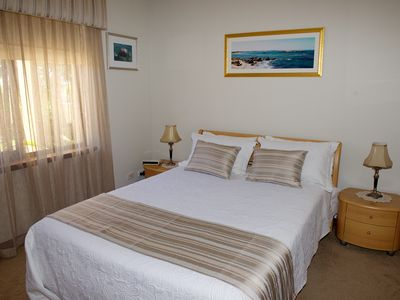 A warm and welcoming Queen size bedroom with loads of storage space.