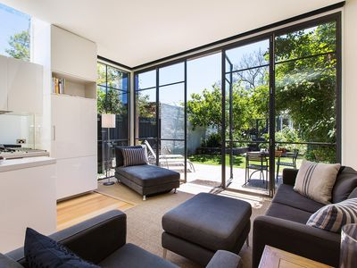 Floor to ceiling windows overlookign leafy private garden