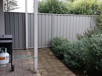The small rear fenced garden has a BBQ and clothes line