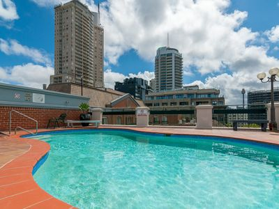Shared rooftop pool with city skyline views