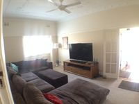 Living room with large comfortable couch, 65 inch LCD/LED TV, cable TV & Netflix