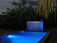 Pool at night with lights on.